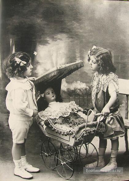 Две девочки разговаривают около коляски