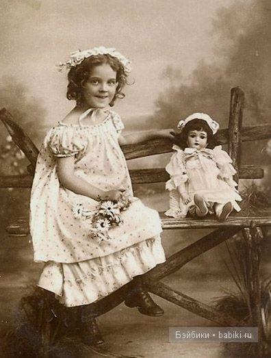 Девочка в чепце, кукла рядом, сидят