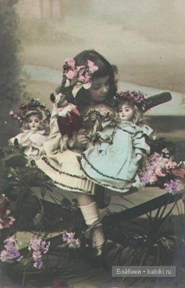 На руках кукла в голубом, девочка склонилась