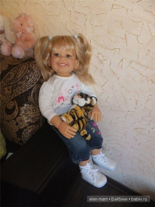 в джинсах, на кресле, с тигрёнком