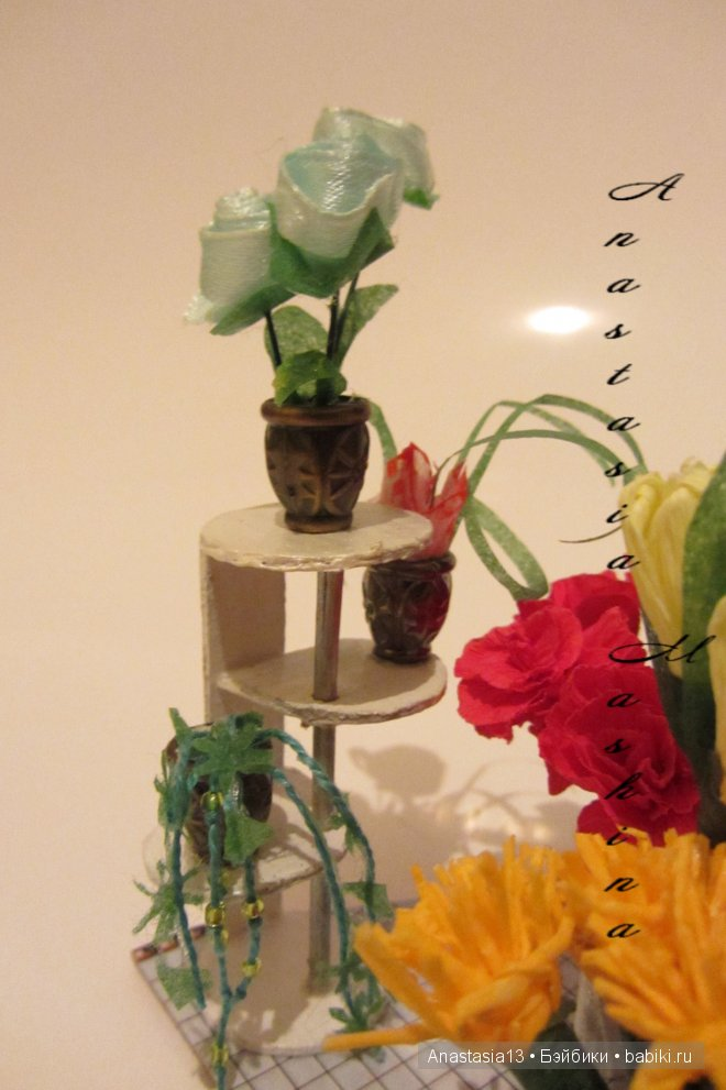 подставка для цветов. В ней цветы в горшках розы, плющ и хлорофитум и