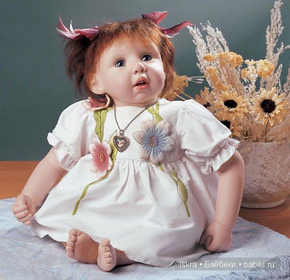 Малышка одета в белое платьице с роскошными объёмными, вышитыми цветами.Рукава-фонарики. Тёмно-рыжие волосики собраны в два хвостика и украшены лентами. Автор  Pat Moulton.