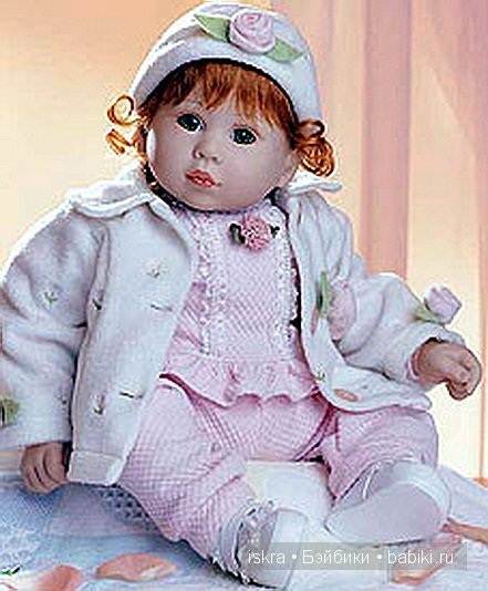 Дженна одета в шерстяную курточку с вышитыми бутонами роз. На голове шапочка с розой. Зелёные глаза и рыжие завитки. Под курточкой розовый трикотажный комбинезончик,а на ножках белые пинетки.