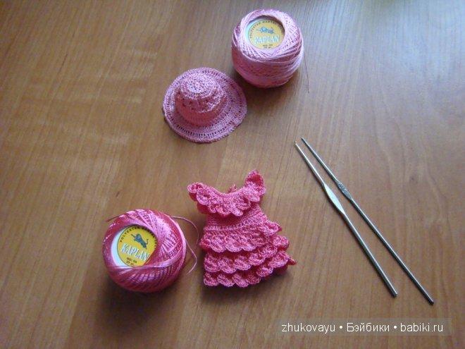 Розовое платье, шляпа и нитки.