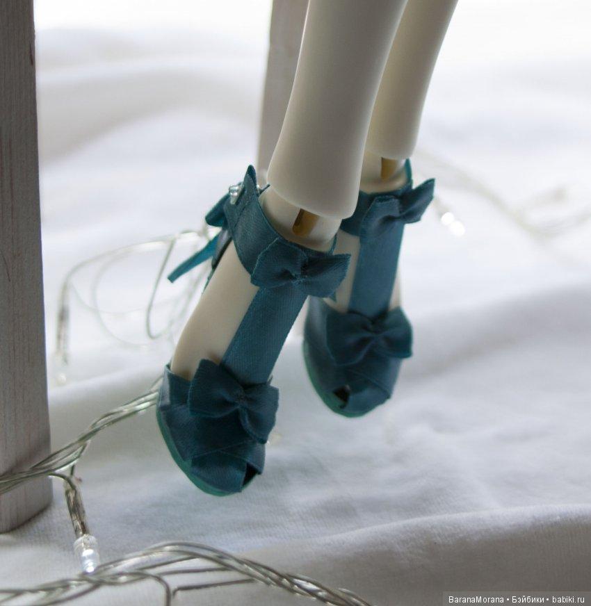 Босоножки из полимеризированного атласа на подошве из натуральной кожи. Каблук выполнен из меди с массивным супинатором, для надежной поддержки куклы в положении стоя. Застежка на кнопку.